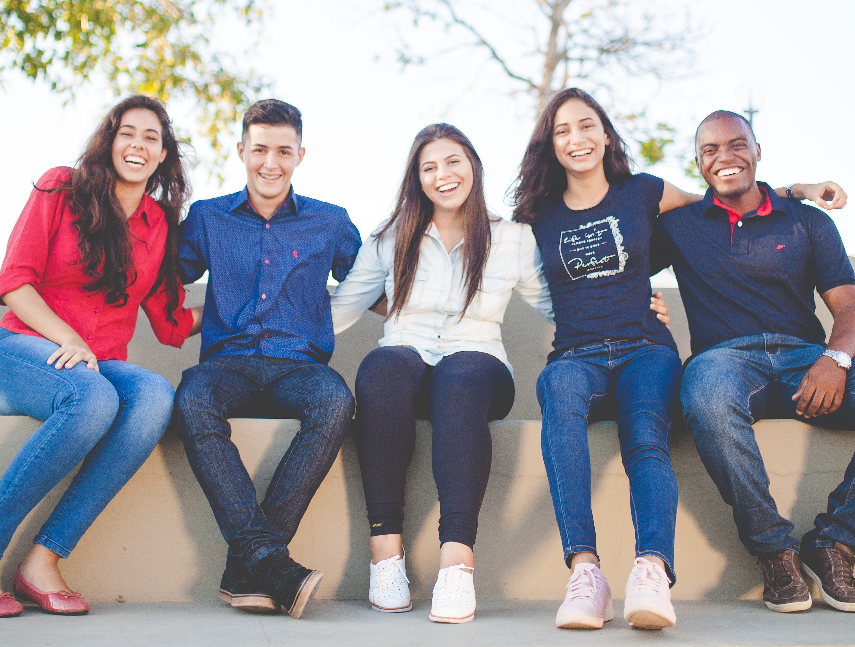 A group of young adults wearing read and blue smiling at the camera.